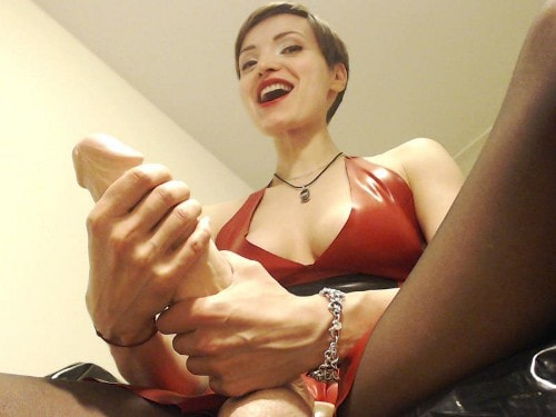 beautiful dominatrix wields strap on dildo